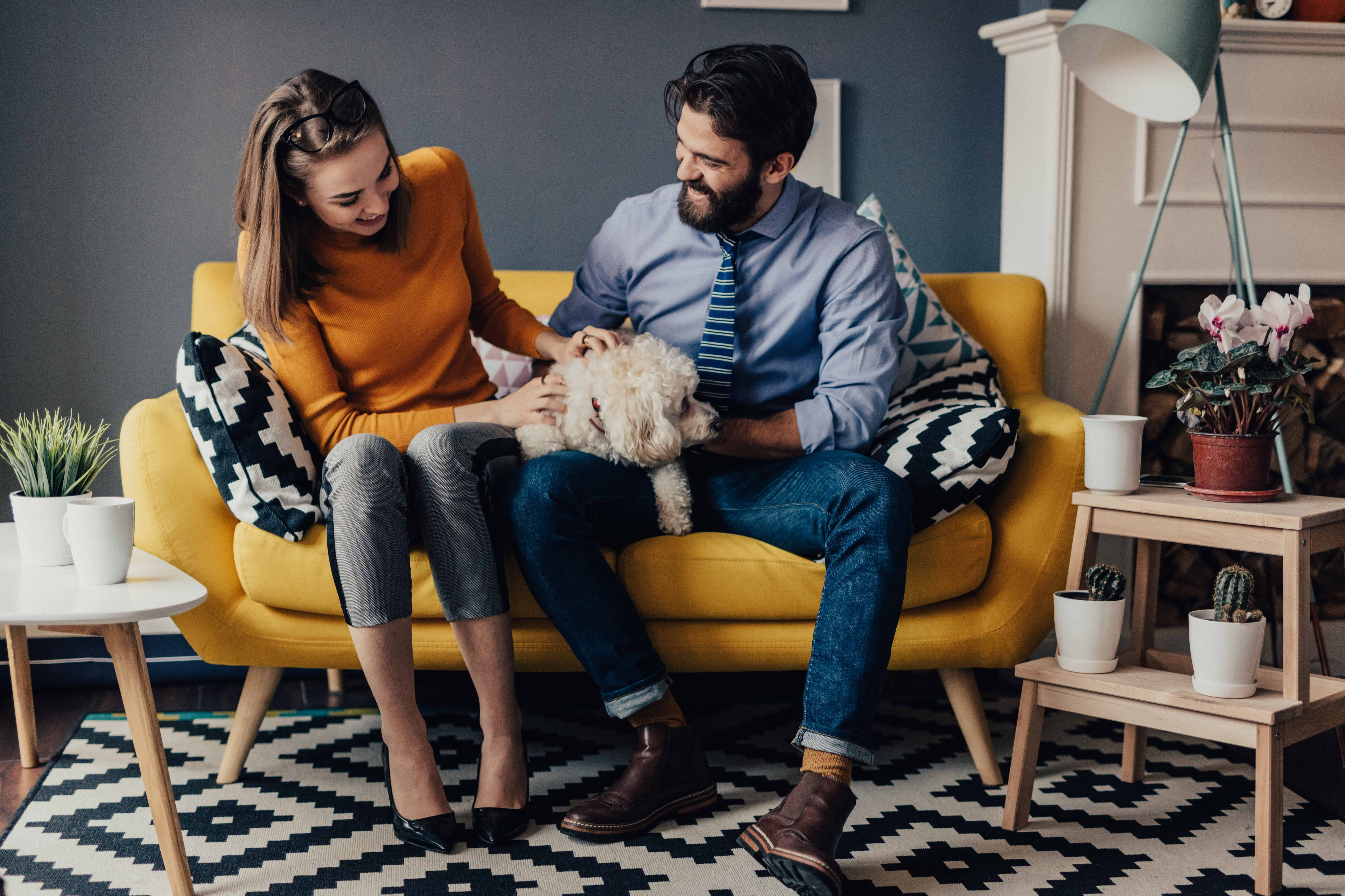 A couple sitting on a couch petting their puppy