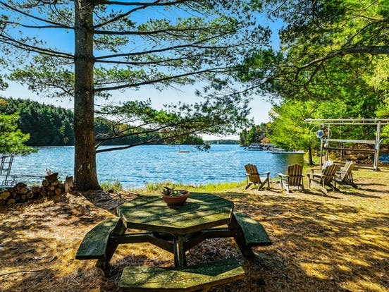 Picnic table and adirondack chairs sit on lawn of lakefront Wisconsin vacation rental