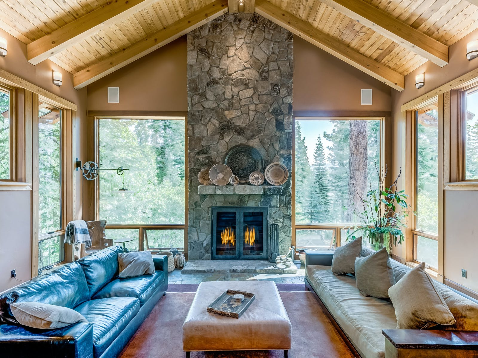floor-to-ceiling windows surround large stone fireplace of Lake Tahoe rental