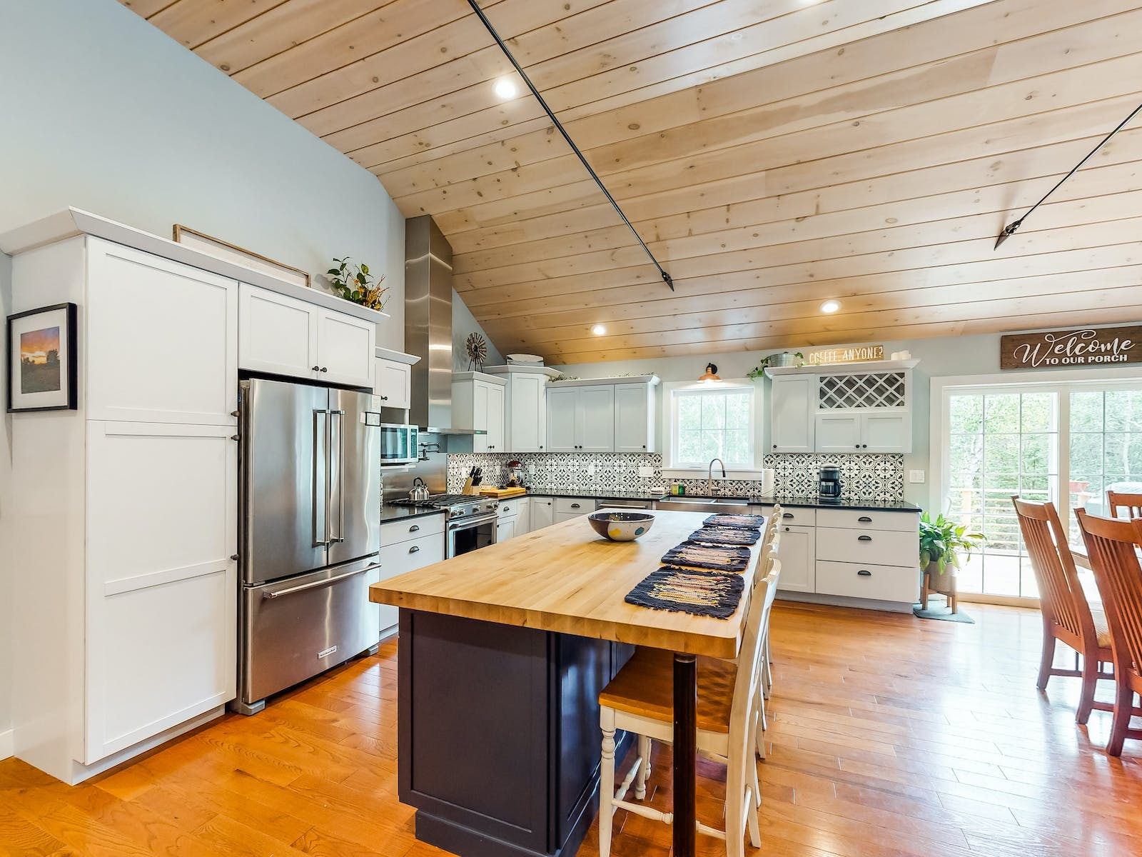 airy, open kitchen with tiled backsplash, stainless steel appliances, and a spacious island
