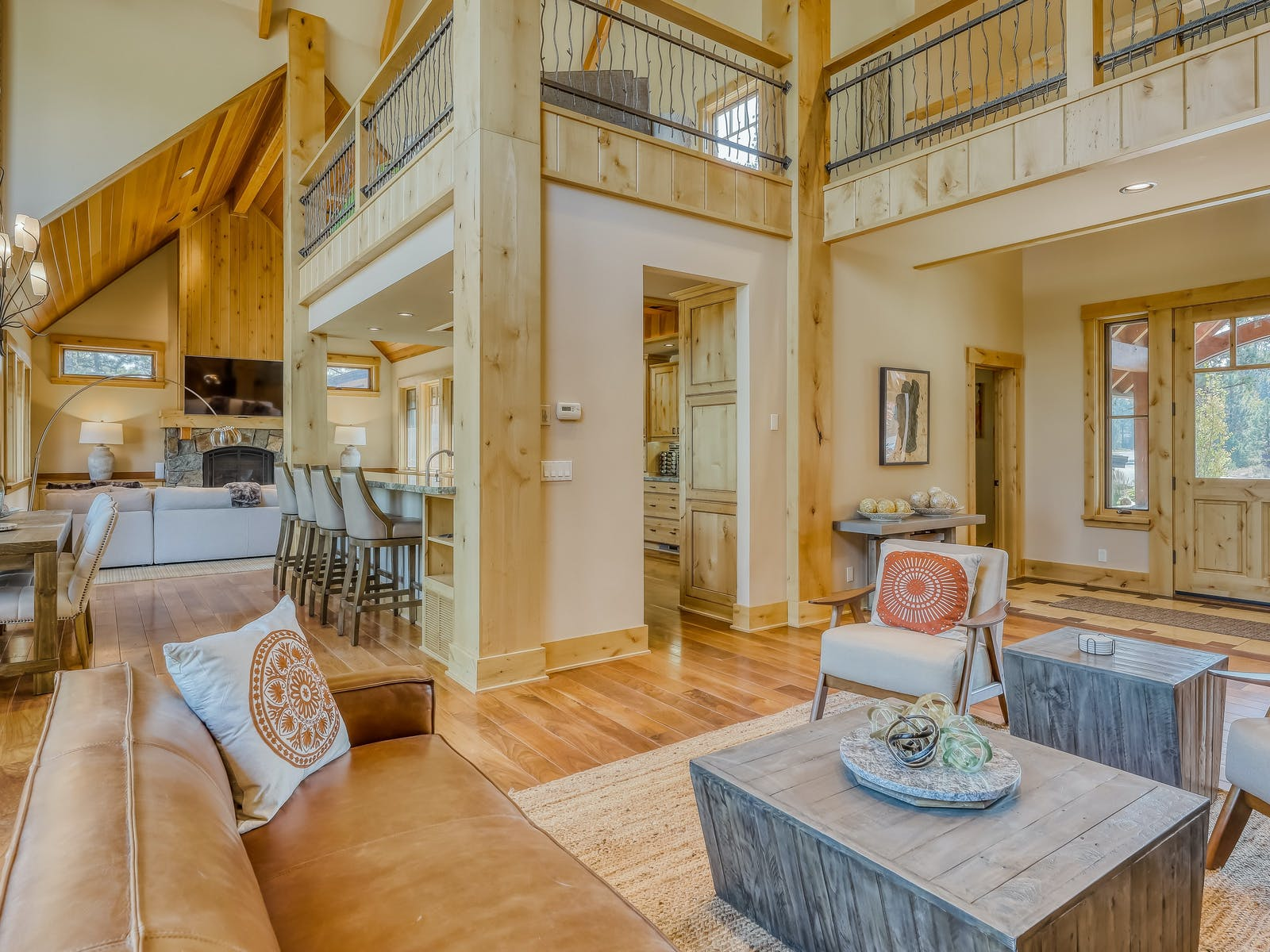 open living space with large leather couch, tall ceilings and loft of Lake Tahoe vacation home