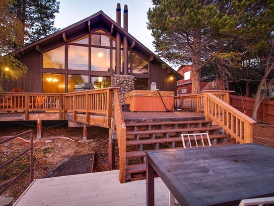 Waterfront vacation rental back deck with hot tub and stairs to table
