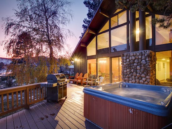 Waterfront vacation rental back deck with hot tub and grill