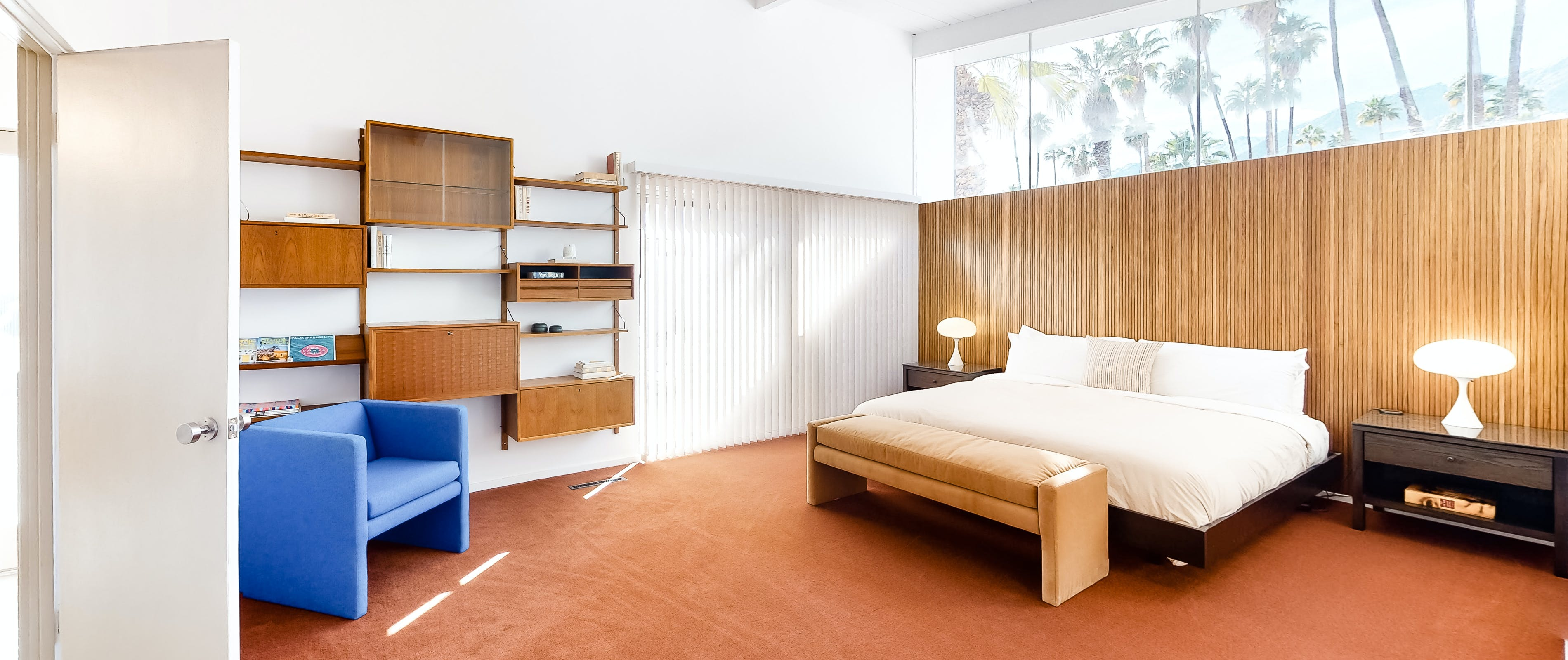 Inside a Palm Springs, CA vacation rental bedroom with large open space, white bed and hanging shelves.