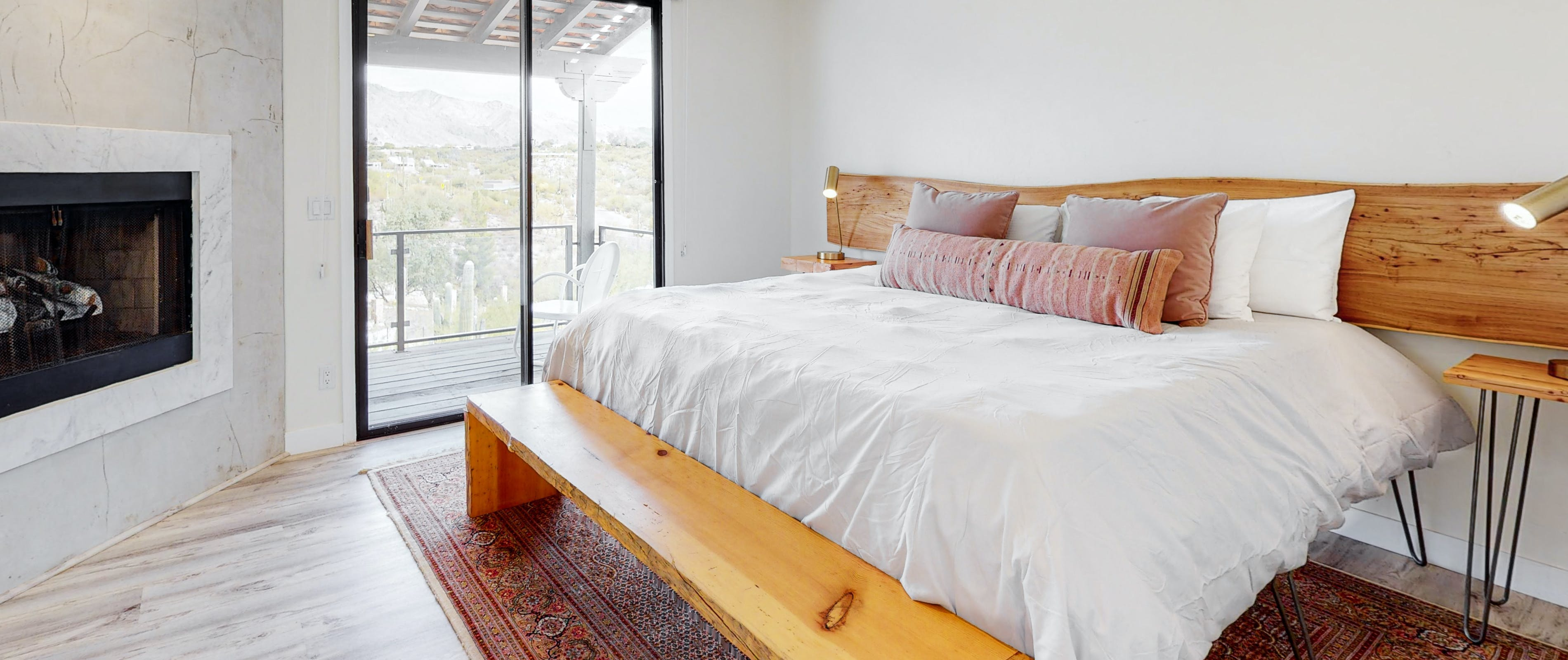 Inside a Tucson, AZ vacation rental bedroom with a white bed, wooden style furniture and fireplace.
