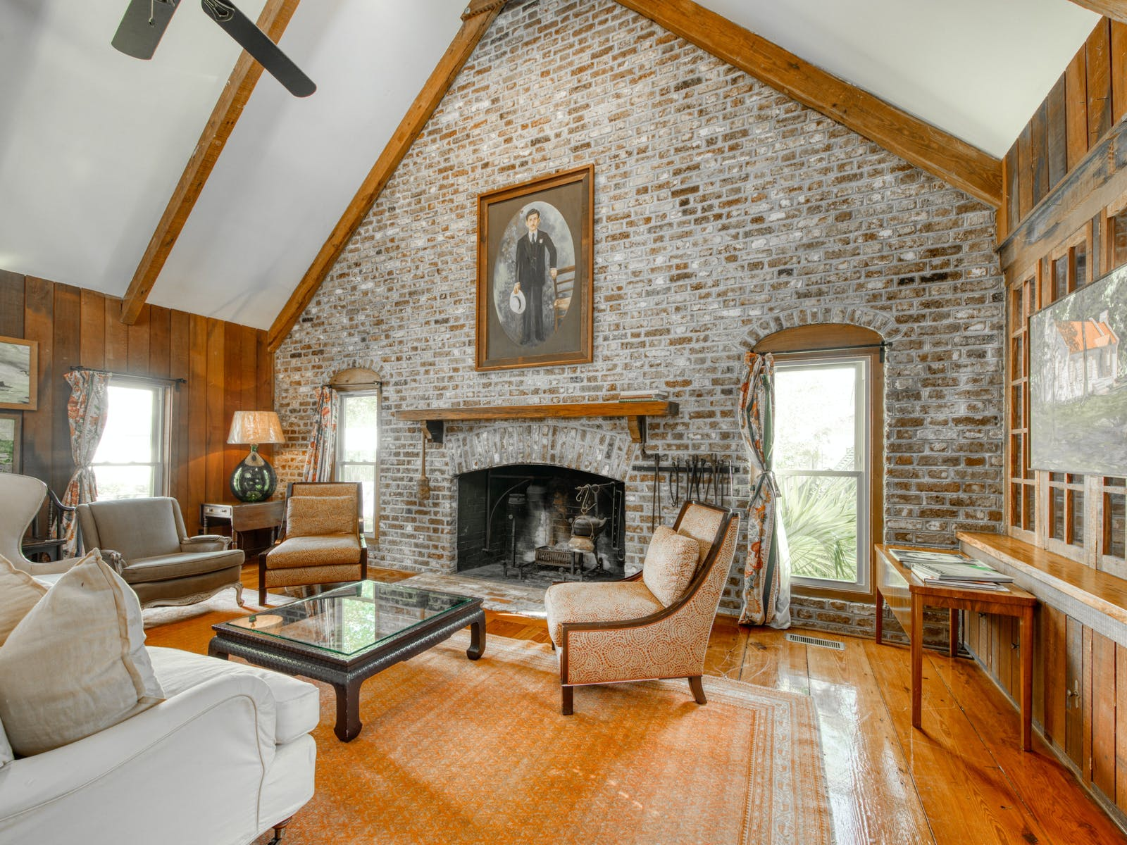 fireplace of South Carolina vacation home framed by antique bricks and vaulted ceilings