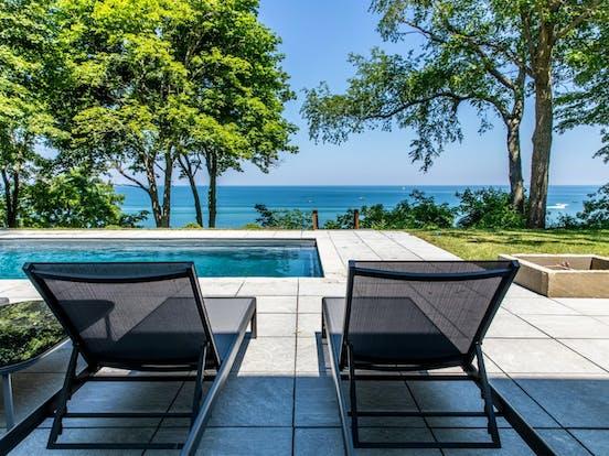 Lounge chairs sit next to outdoor pool facing Lake Michigan