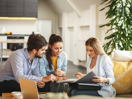 vacation home buyers sitting with their real estate agent
