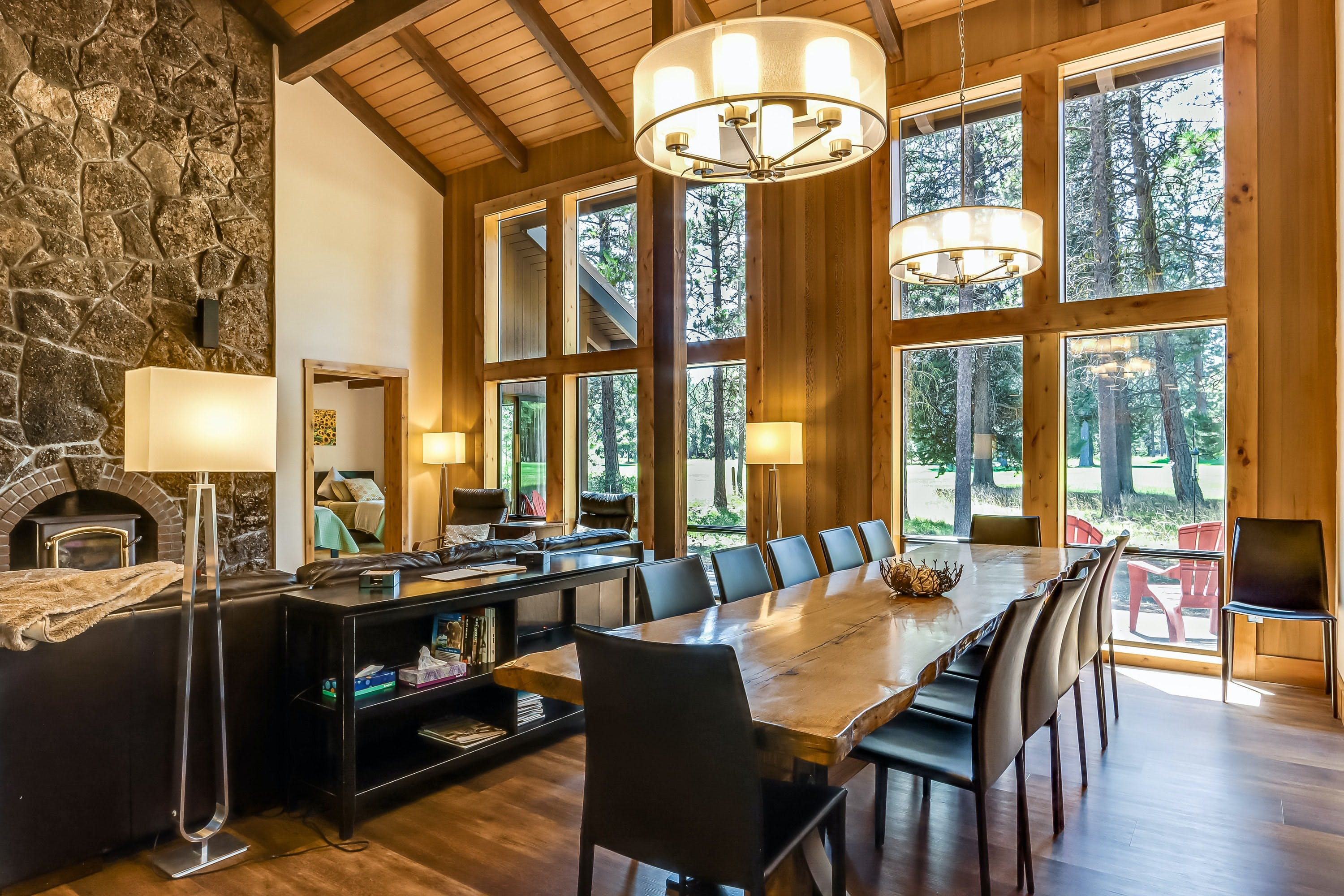 large dining table and stone fireplace inside Black Butte, Oregon vacation home