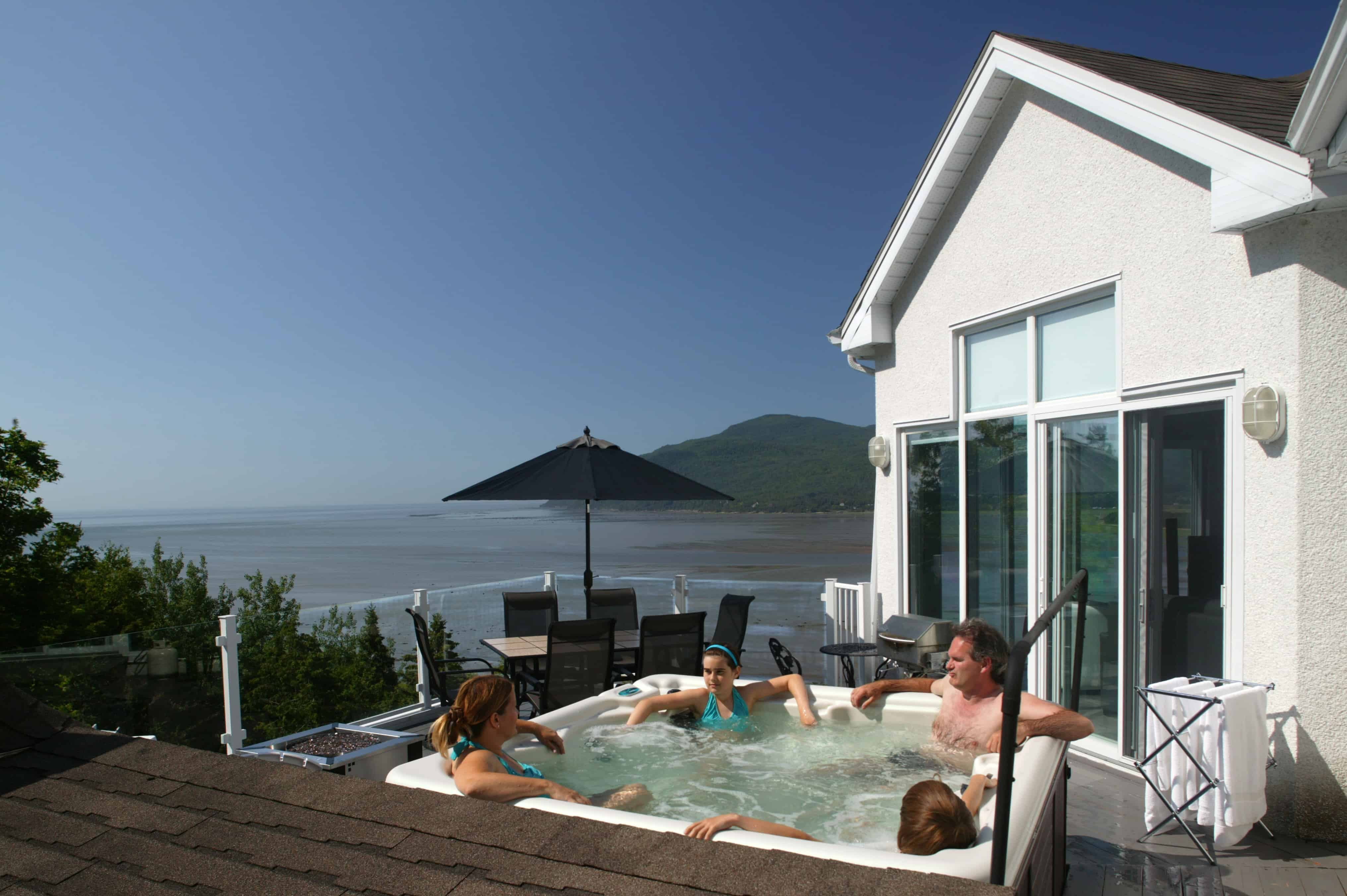 a group of friends relaxing in a hot tub that overlooks the ocean
