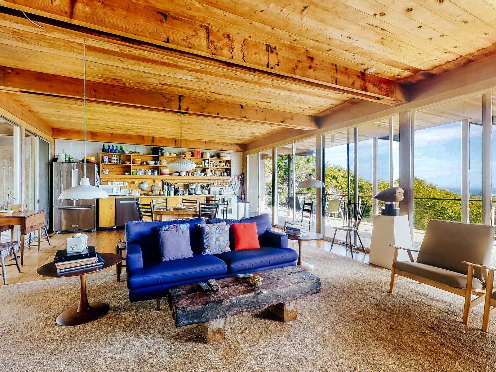 Exposed wood beams and open layout with a blue coach and beautiful views in Chilmark, MA.