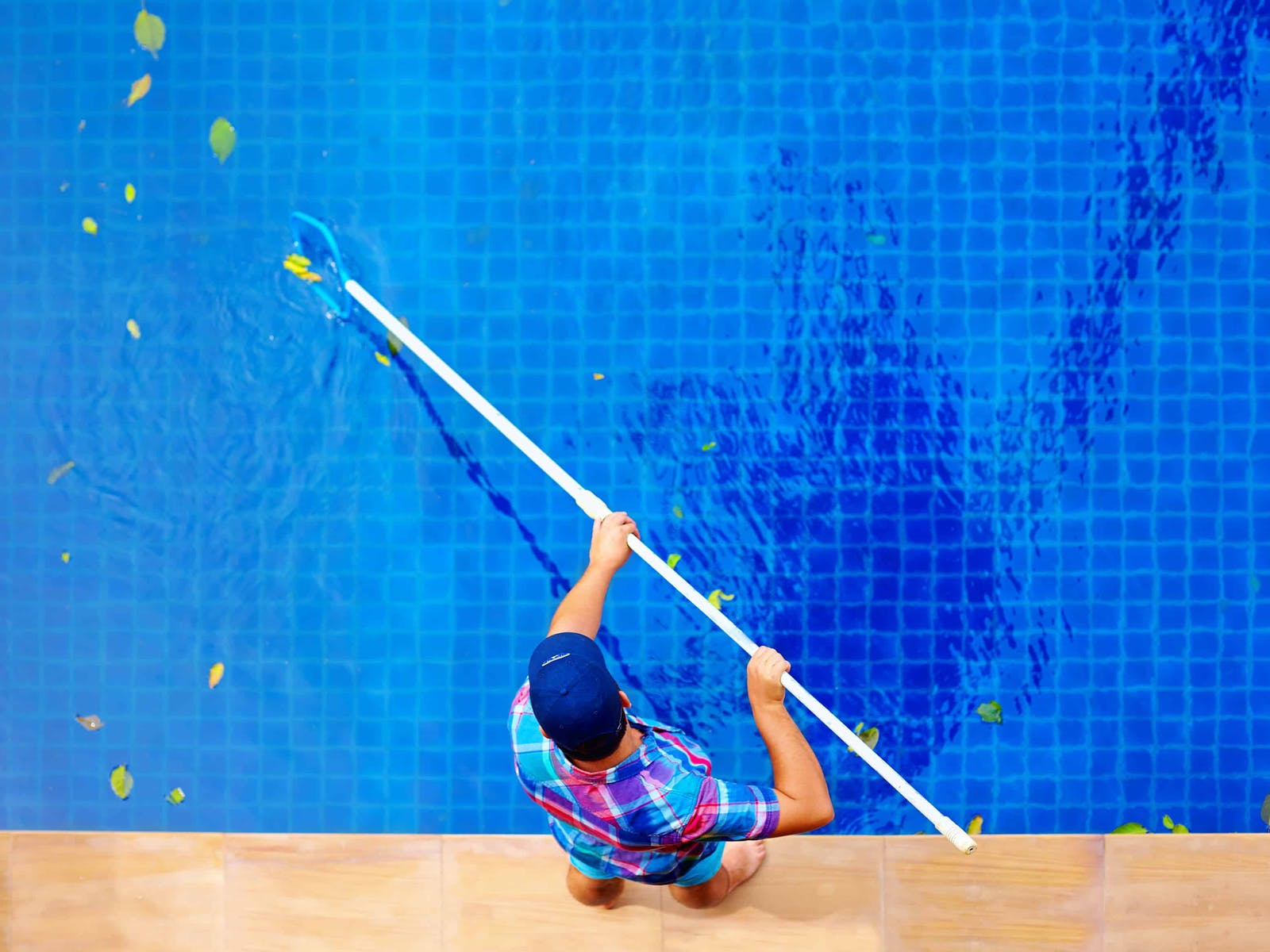 An employee cleaning leaves out of a pool