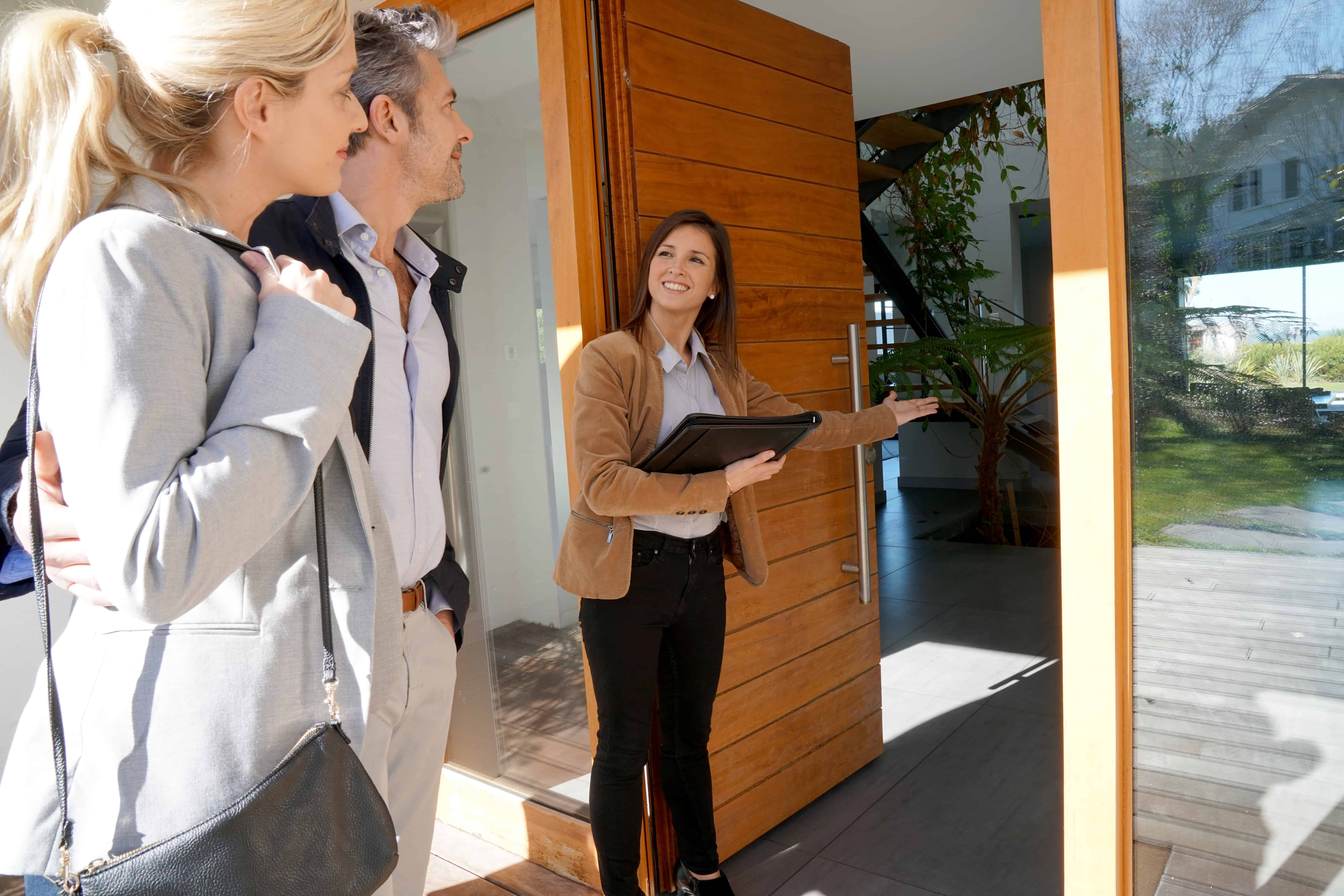 real estate agaent welcoming in buyers to a home