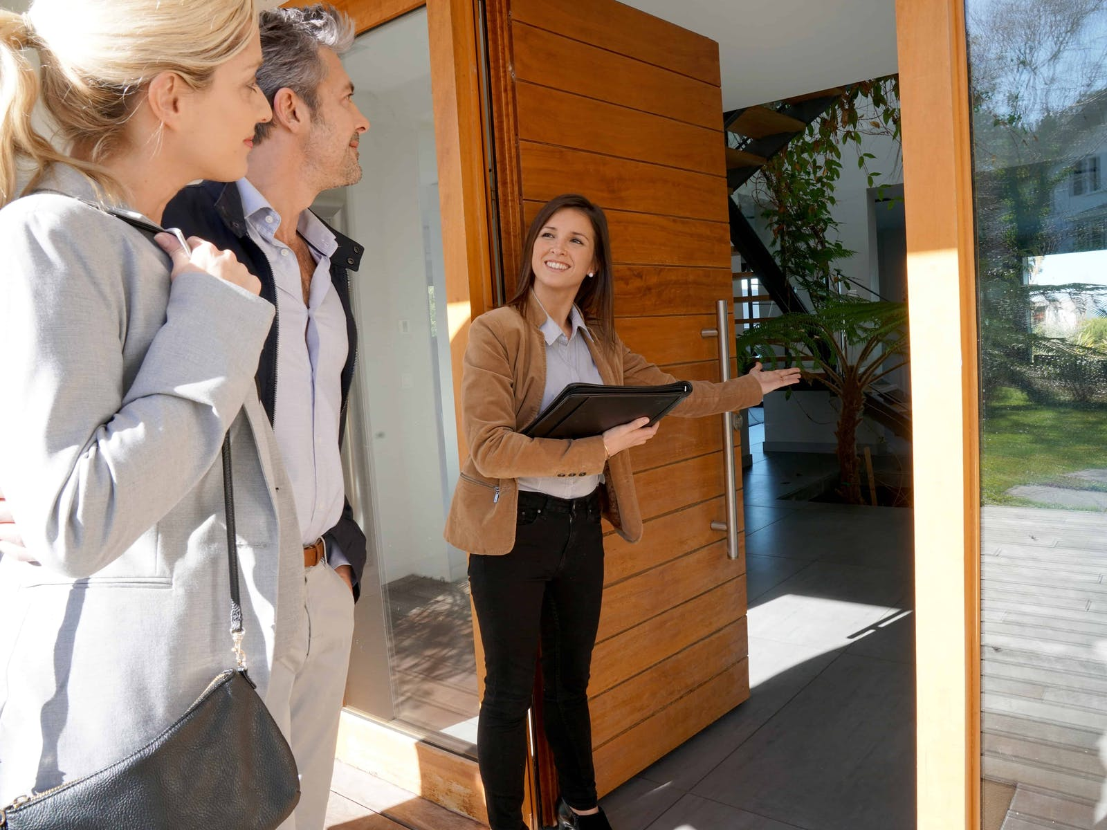 real estate agent welcoming potential buyers into a home