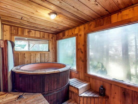 A indoor hot tub and sauna in a vacation rental in the woods