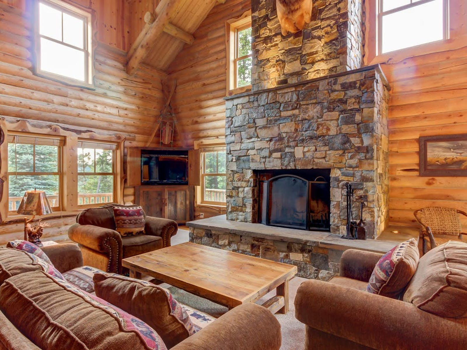 interior of vacation cabin with large stone fireplace, lots of couches and ample natural light