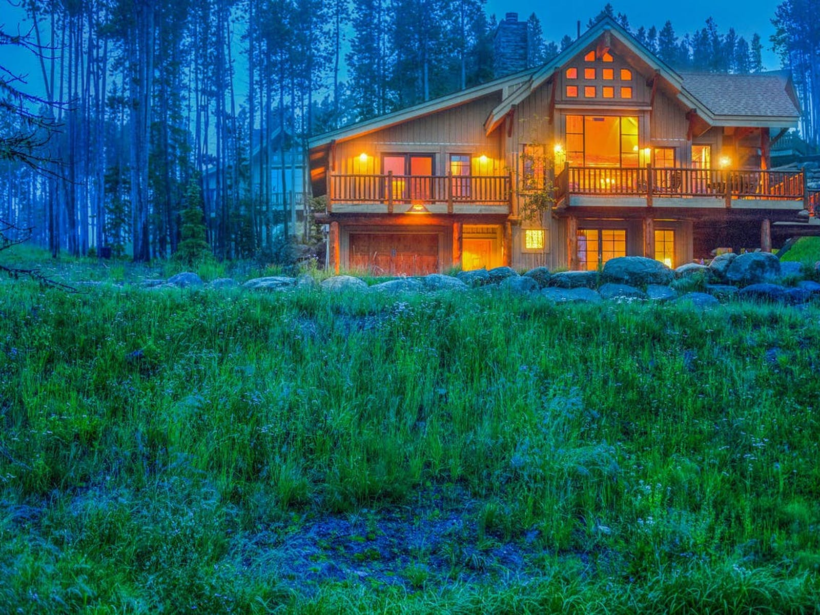 large vacation home in big sky, mt surrounded by trees and meadow