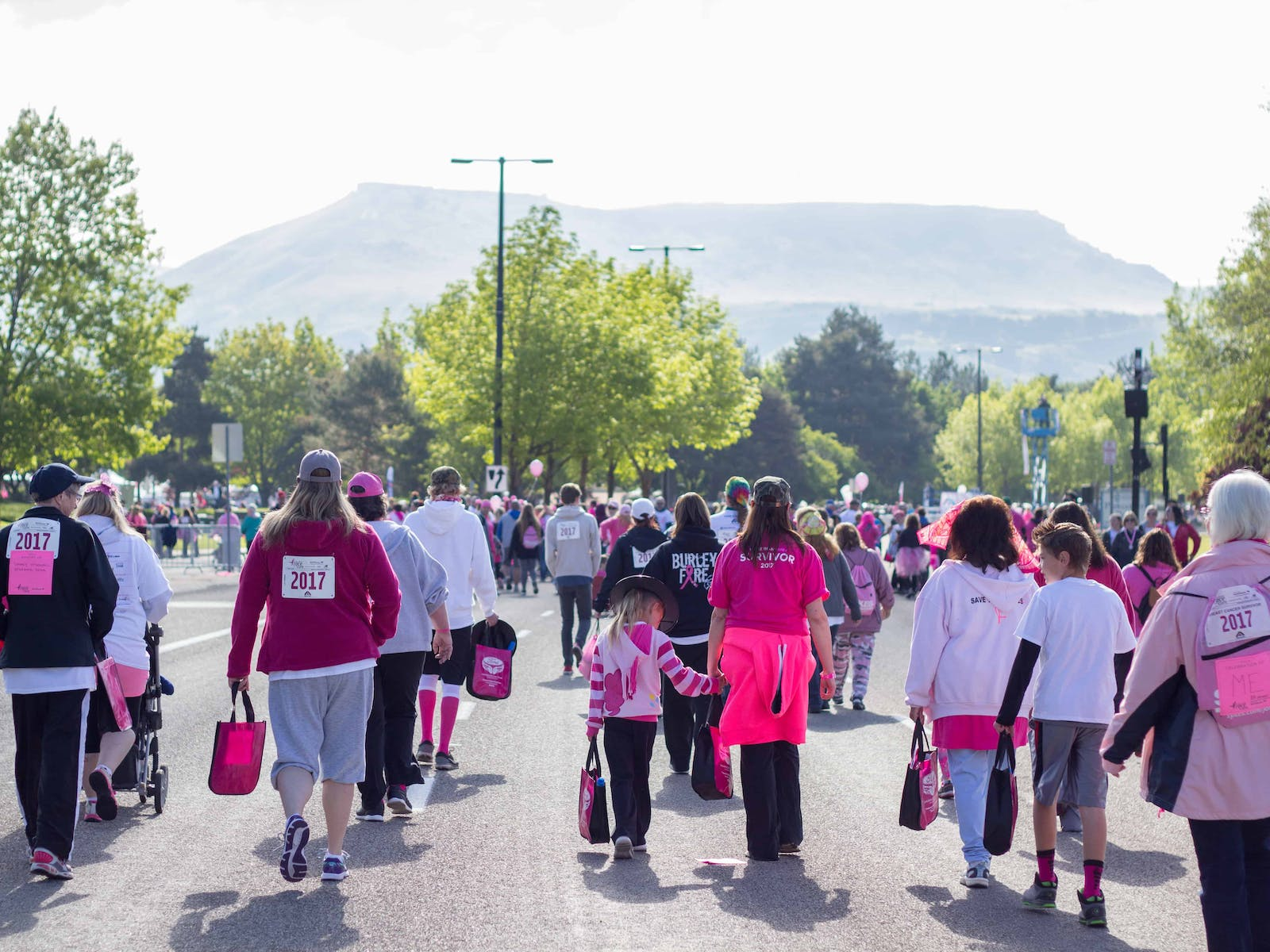 a large group of people doing a charity walk for breast cancer