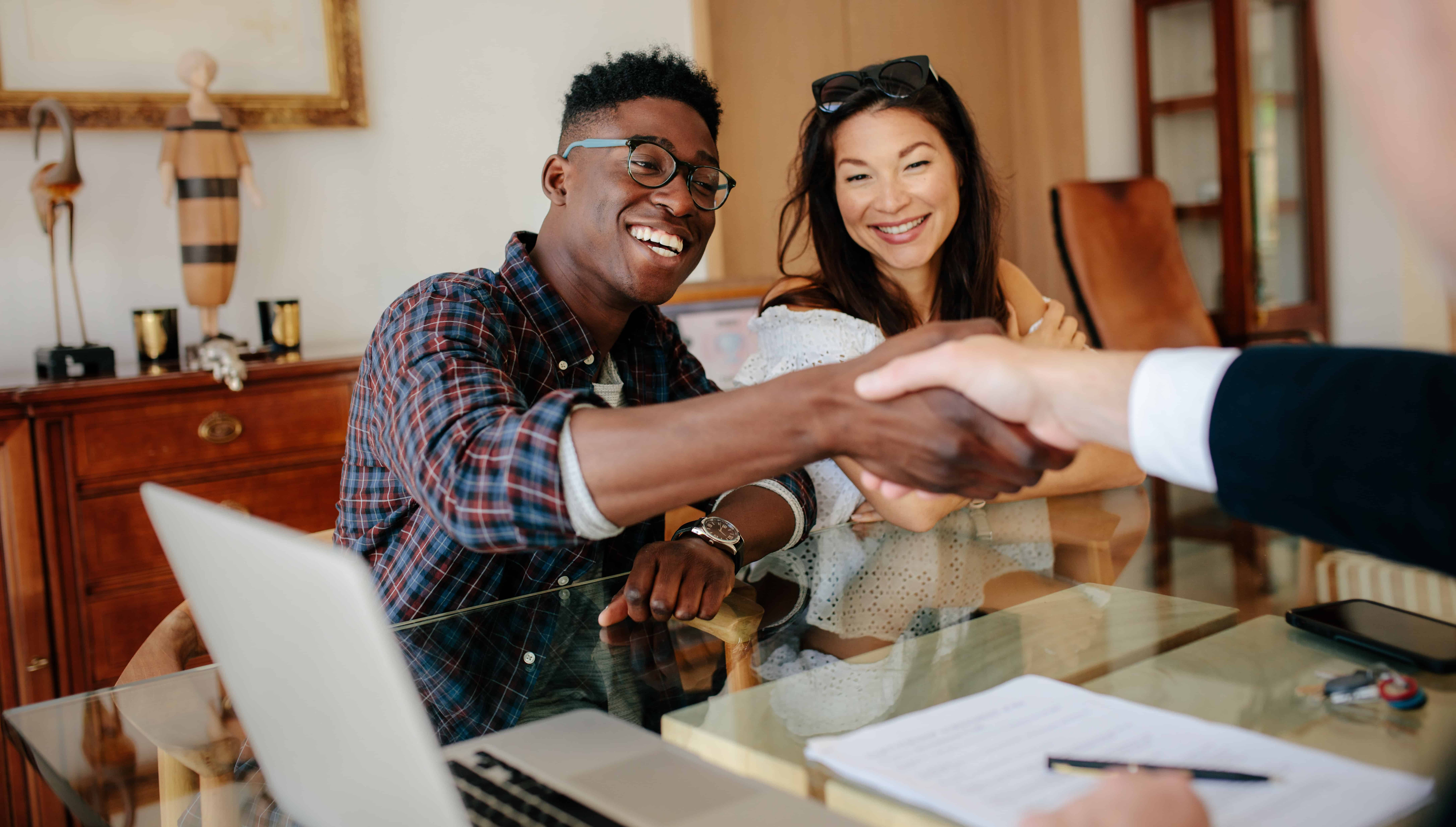 home buyers shacking hands with their real estate agent