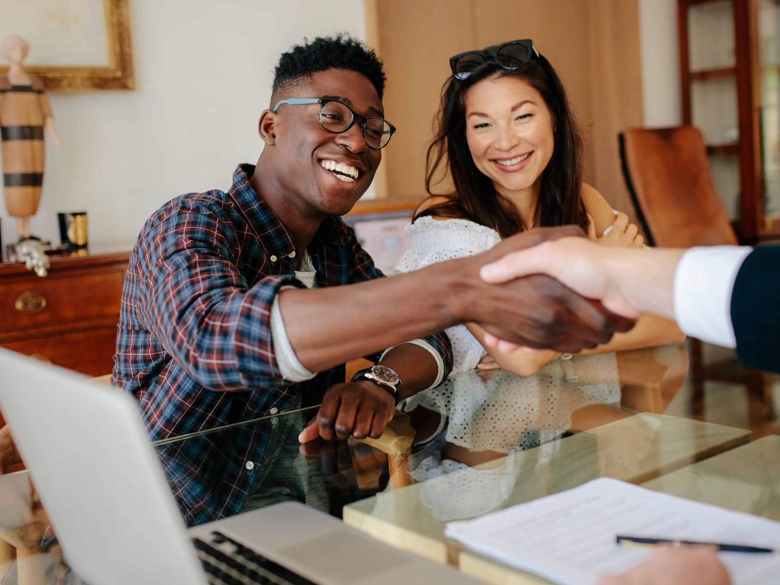 home buyers shaking hands with their real estate agent