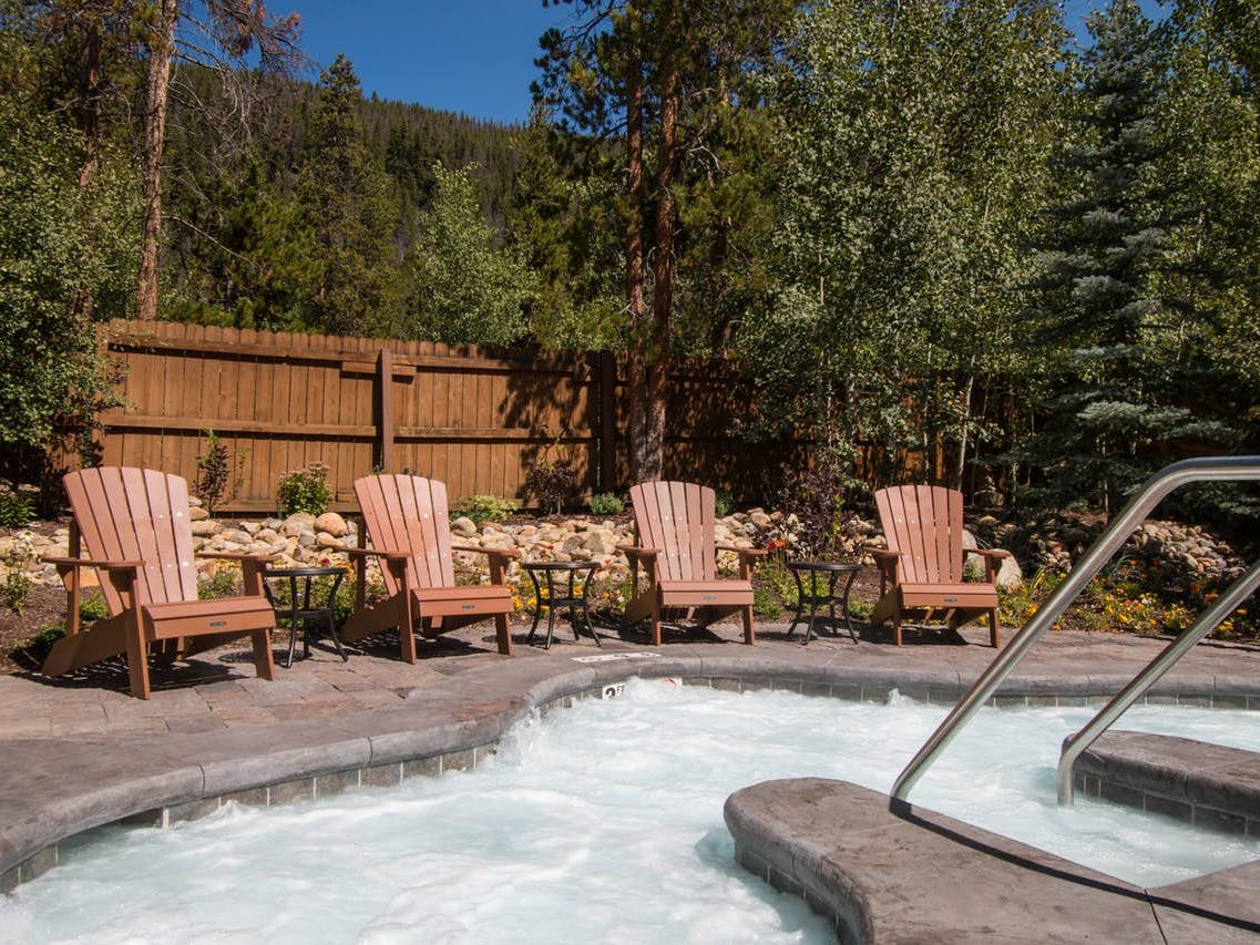 outdoor hot tub surrounded by adirondack chairs