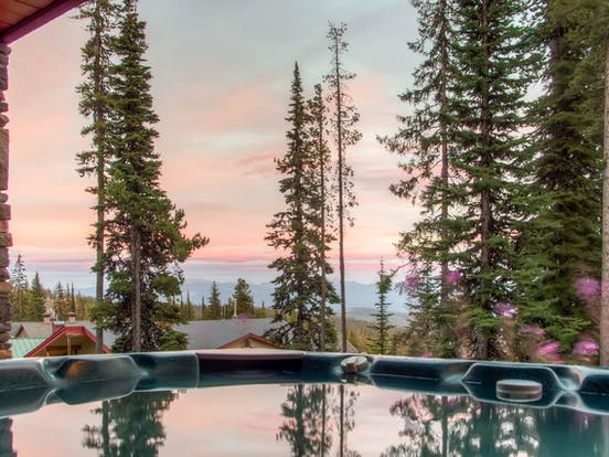 big white cabin with outdoor hot tub