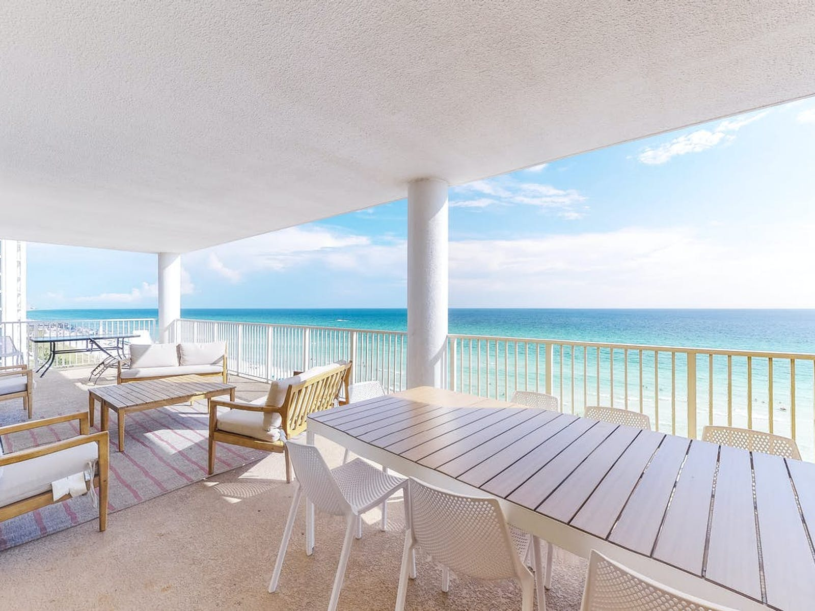 balcony of pcb oceanfront condo decorated with warm wood furnishings and gray tones