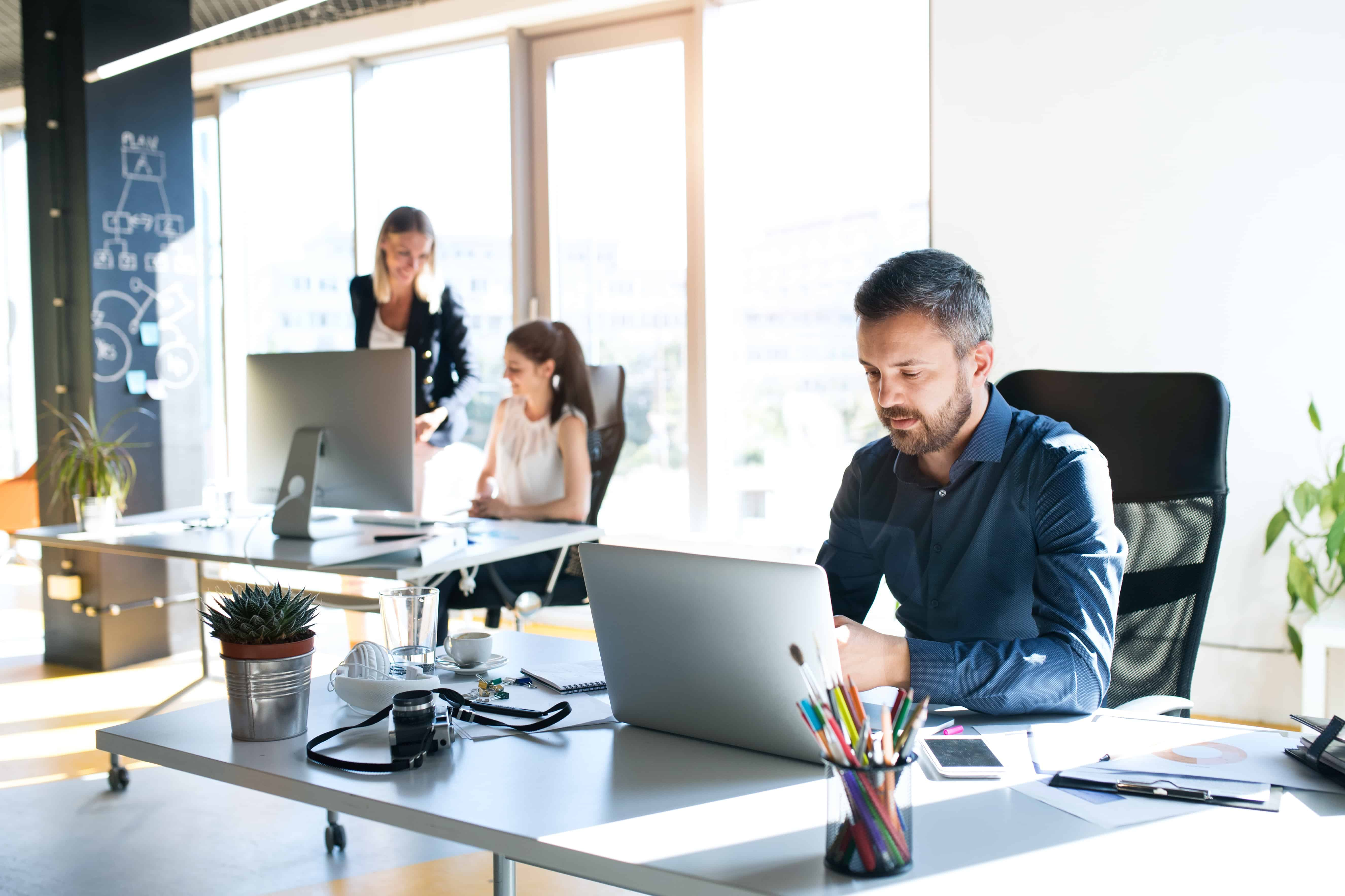 3 people sitting at their desks in a modern office space