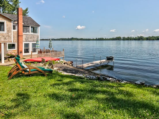 lakefront vermont vacation home with lounge chairs and dock