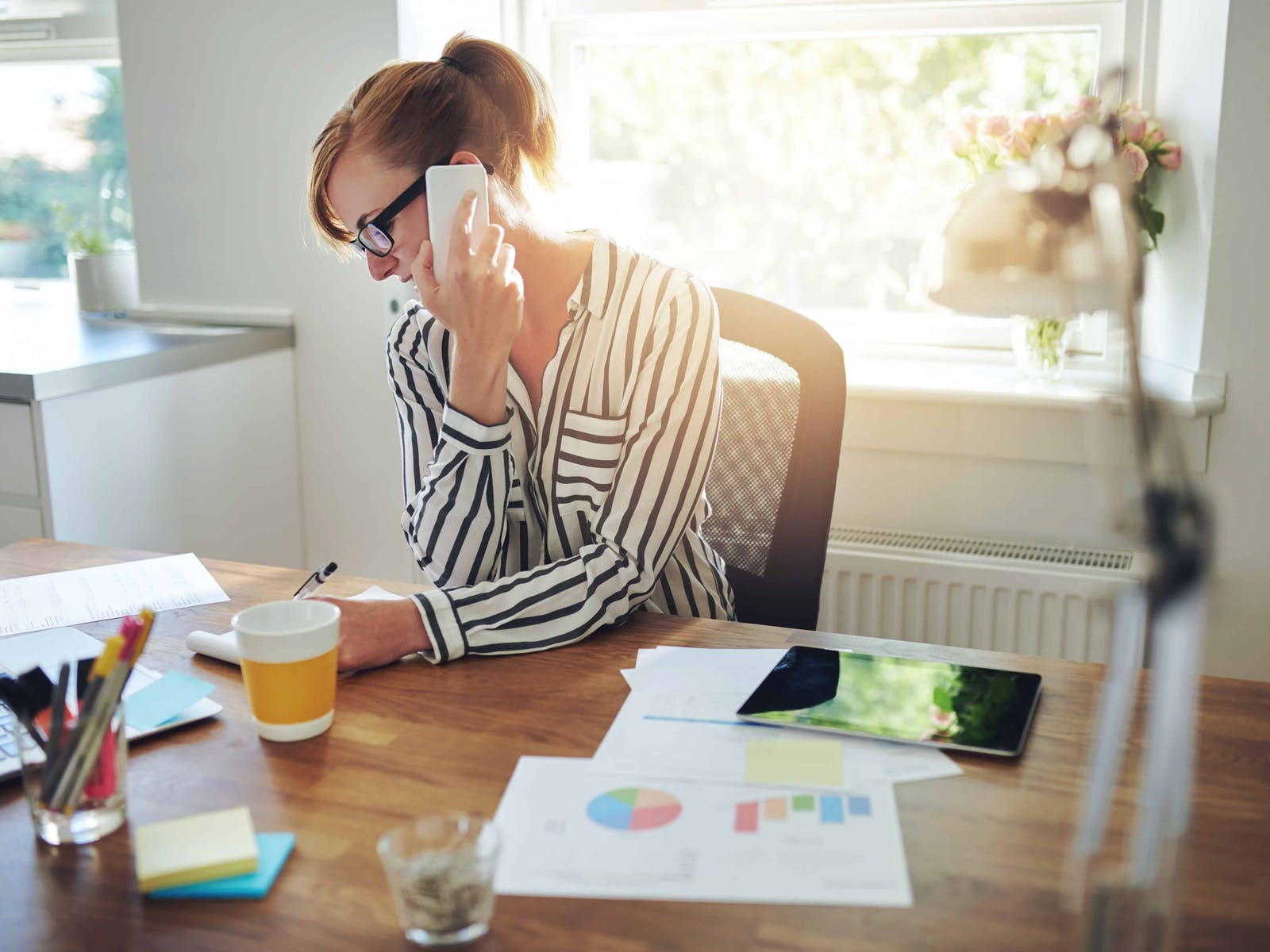 a woman sitting at her desk on the phone with a client