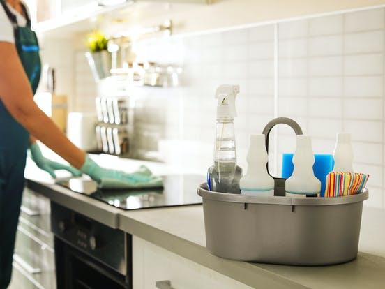 housekeeper cleaning the stove with a bin of cleaning supplies sitting on counter