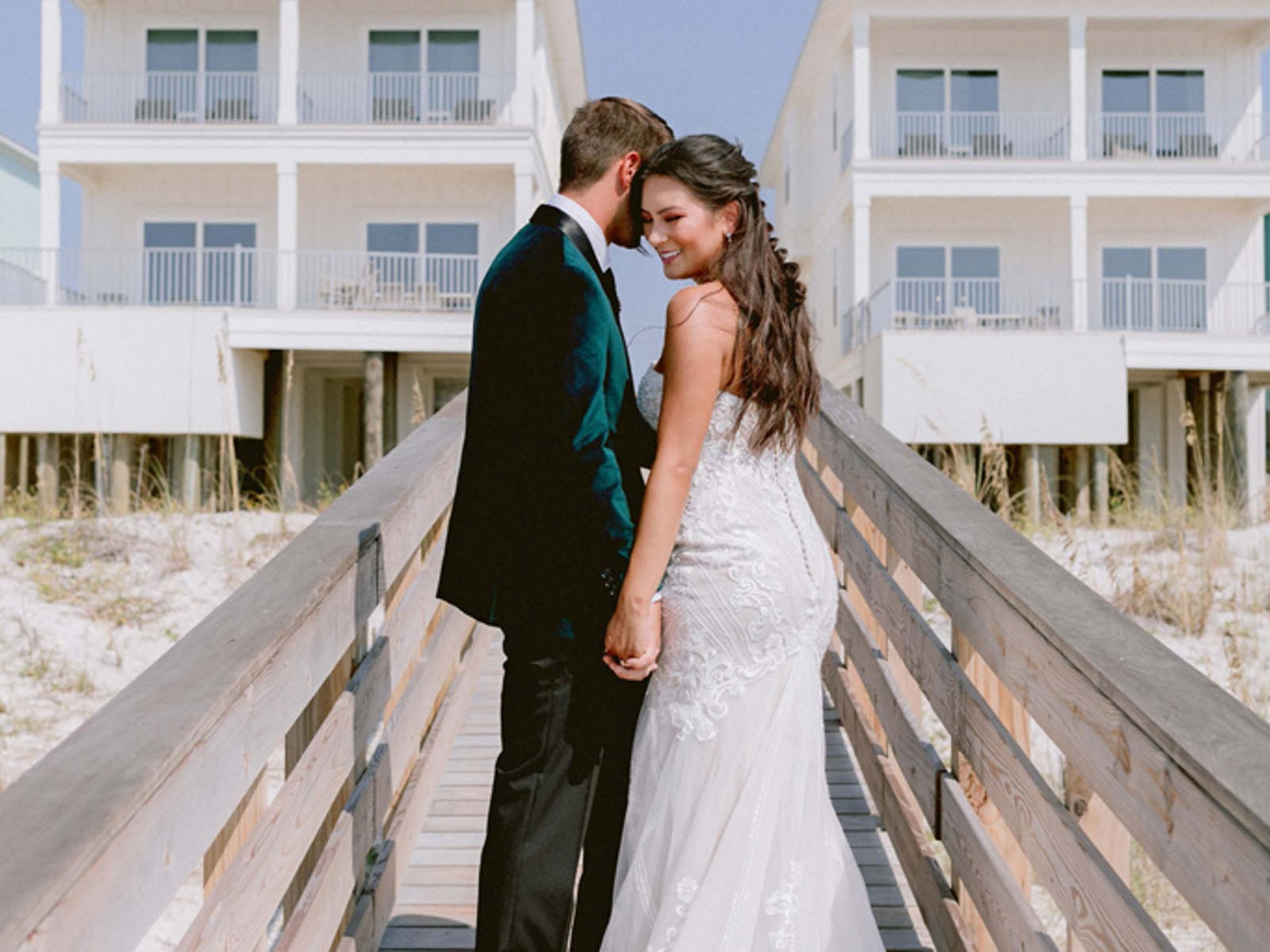 Wedding photo taken on the boardwalk to the beach at a vacation rental
