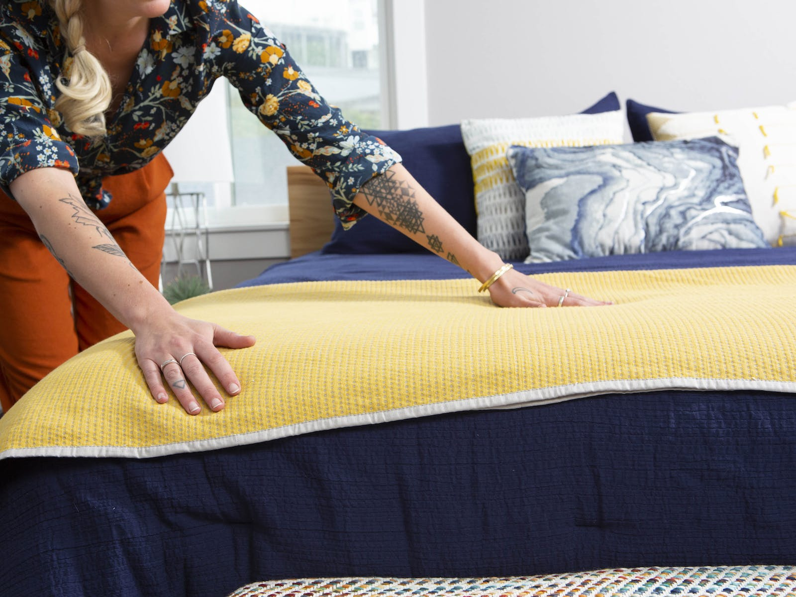 Woman making bed in vacation rental