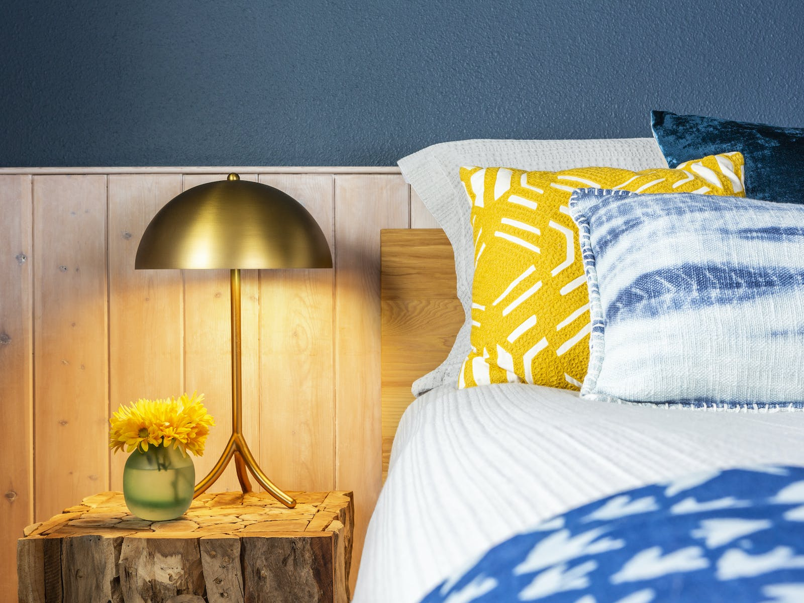 Bedside table with lamp and flowers in vacation rental bedroom