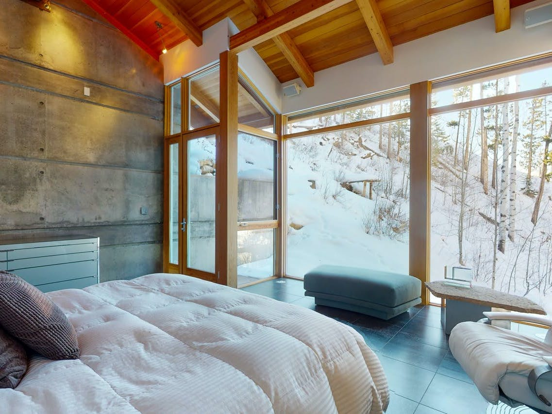 A cozy vacation home room with modern furniture and floor-to-ceiling windows in Gore Creek, CO.