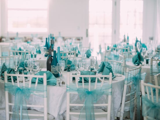 Indoor wedding reception set up with turquoise accents