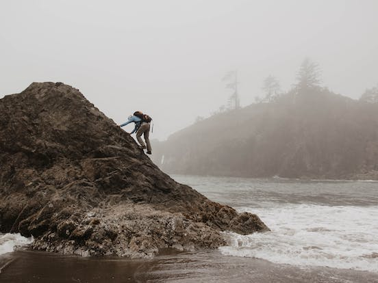 Hiker climbs a La Push beach rock formation