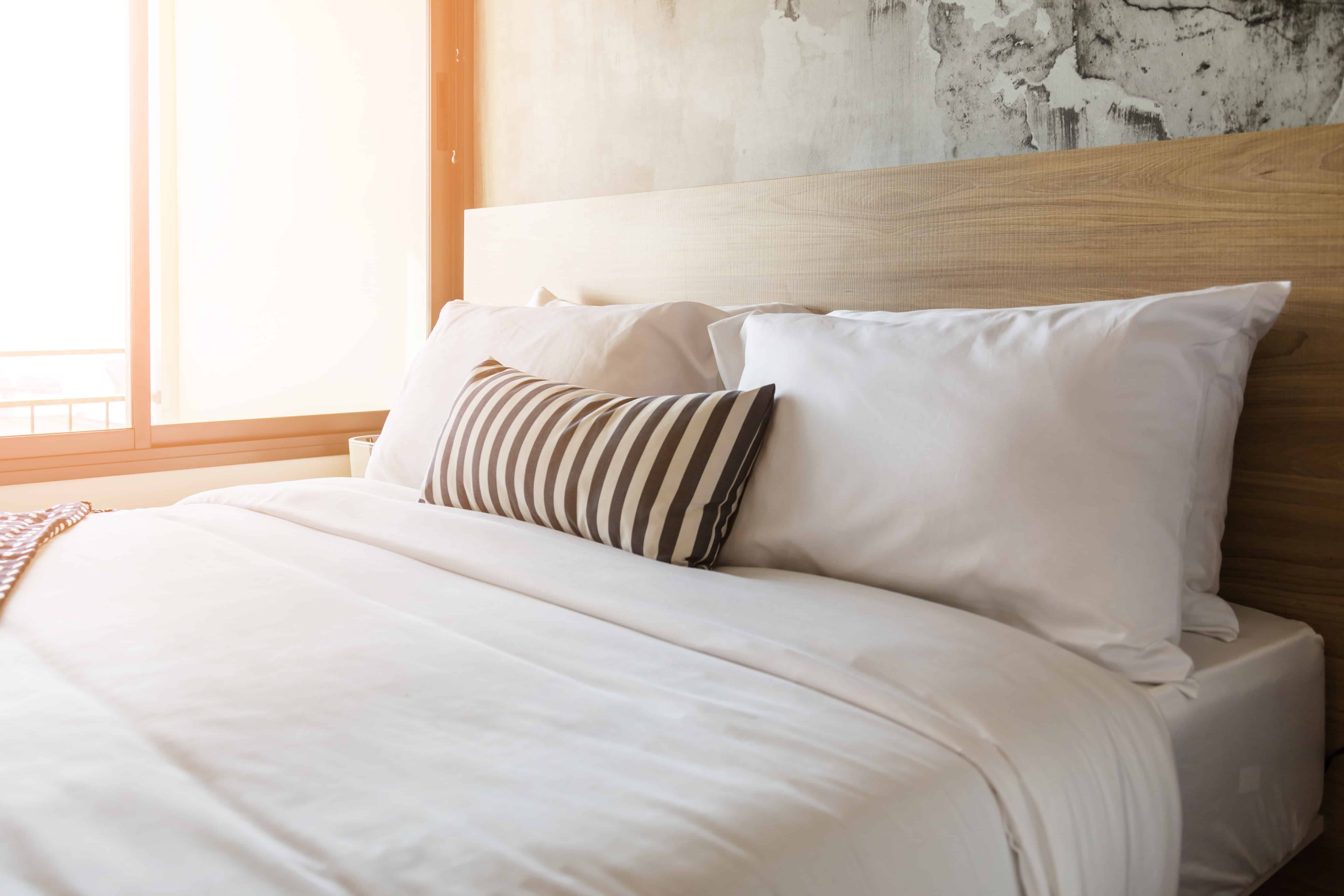 a well-made bed with white linens