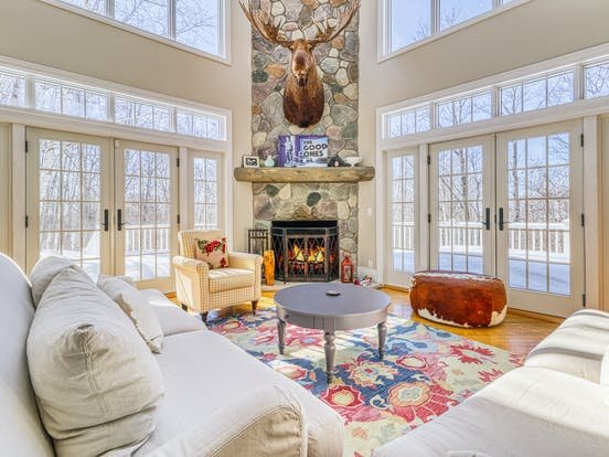 Harbor Springs, MI vacation home featuring french doors leading out to a large deck and a stone fireplace