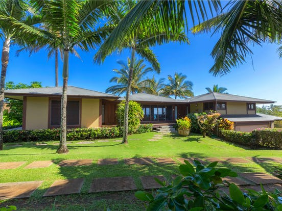 Beach house rental exterior and lawn with palm trees