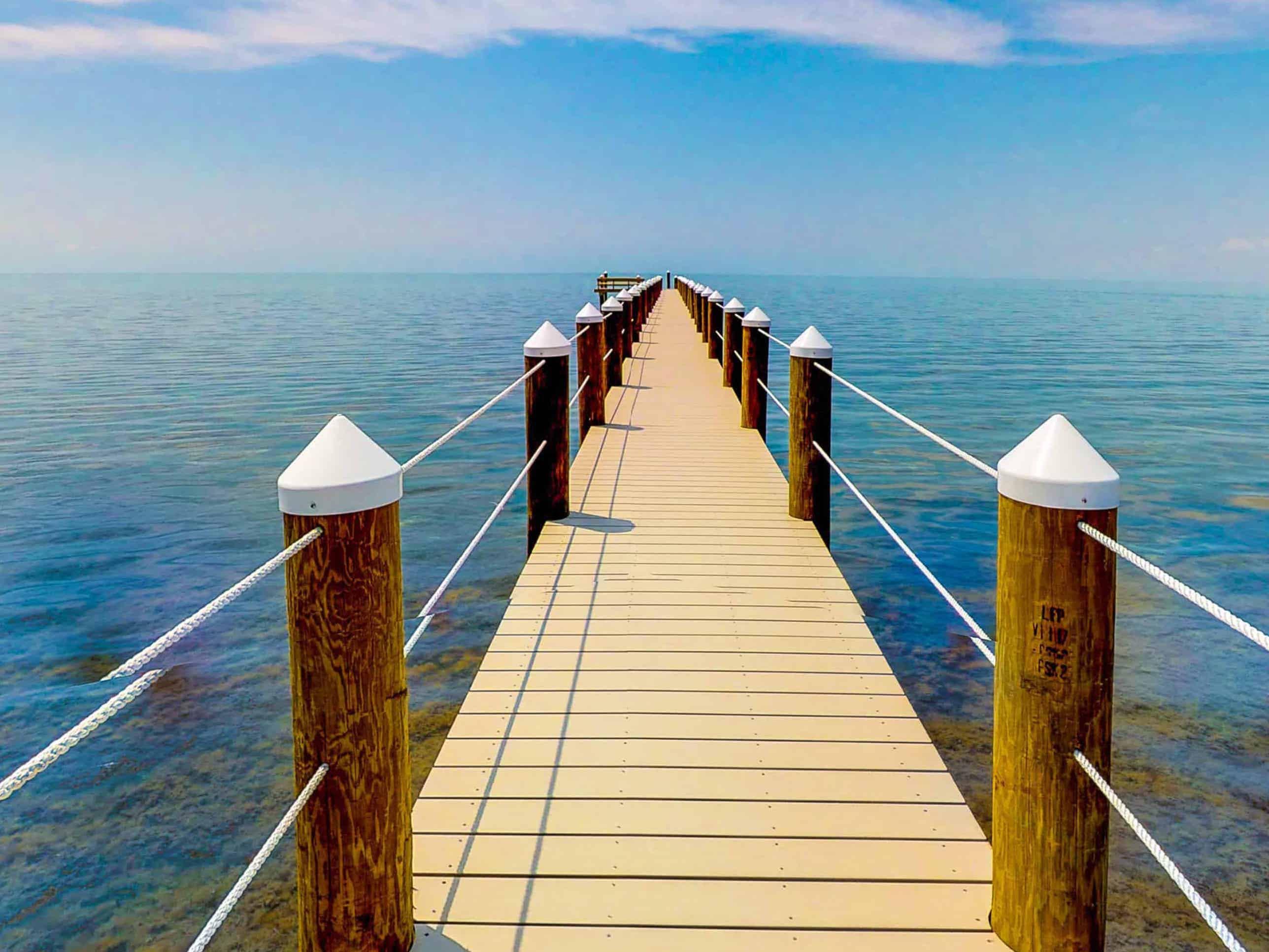 a dock leading into the ocean in marathon, florida