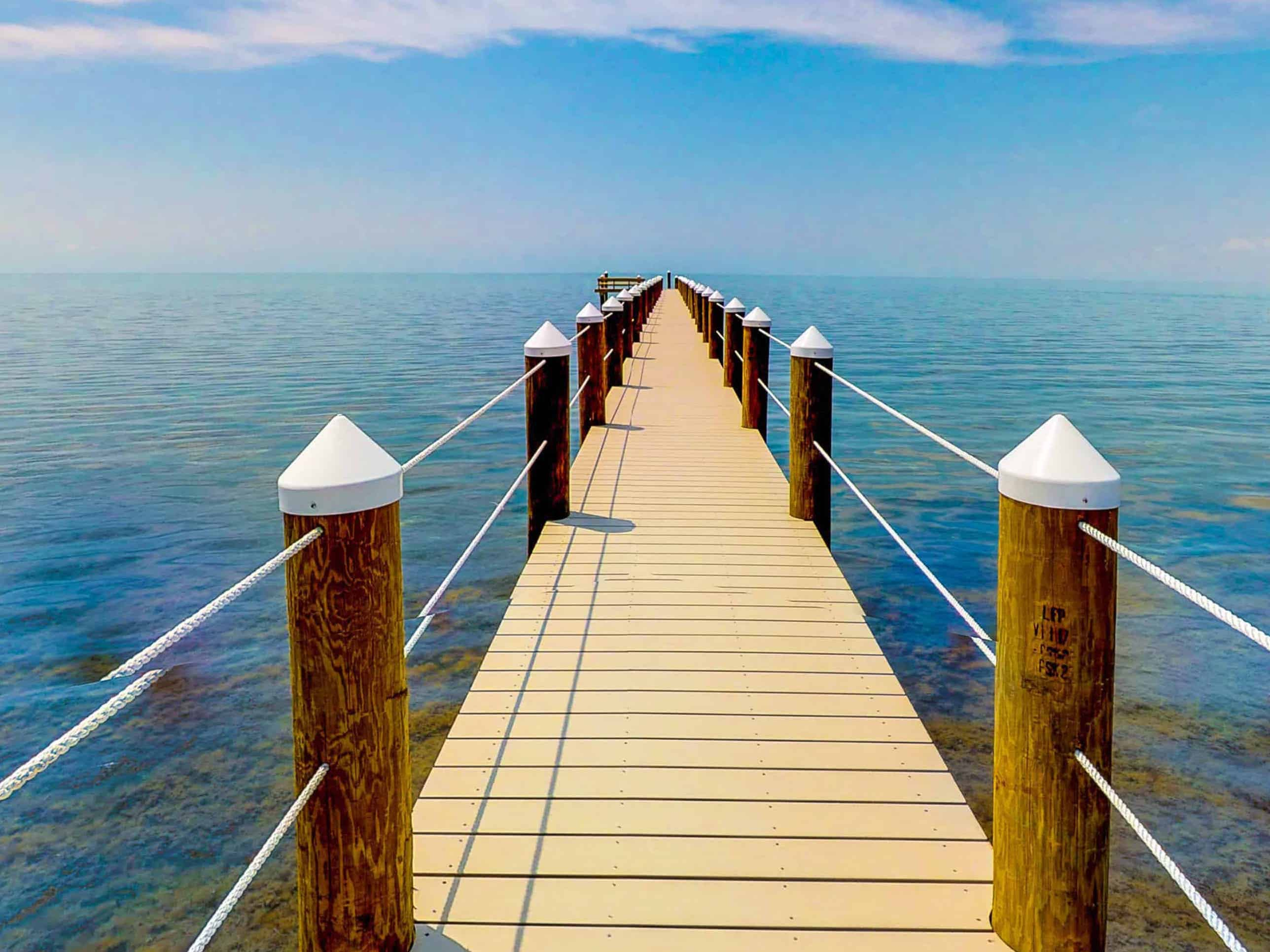 a dock leading into the ocean in marathon, florida