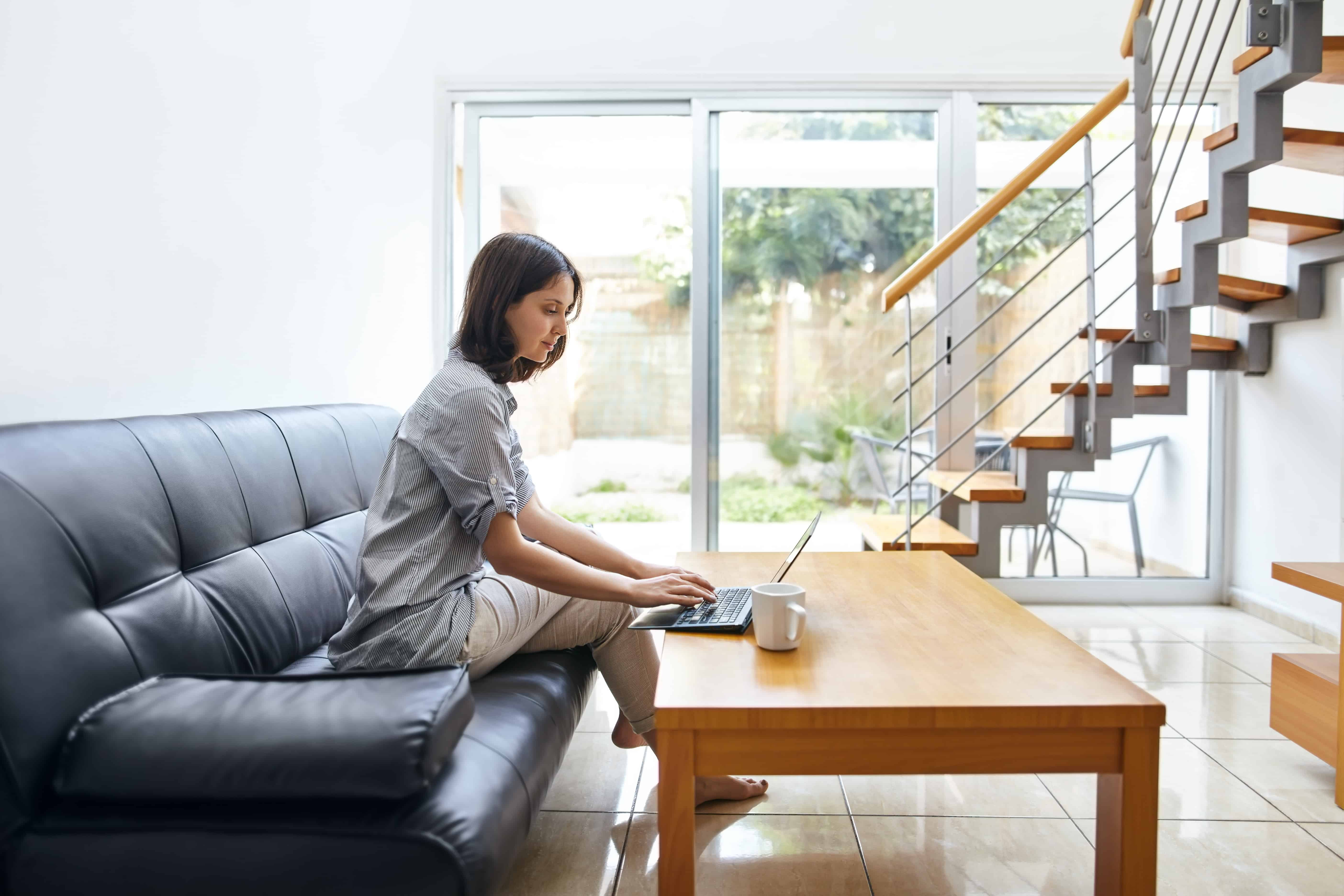 a woman working on the couch in her multifamily unit