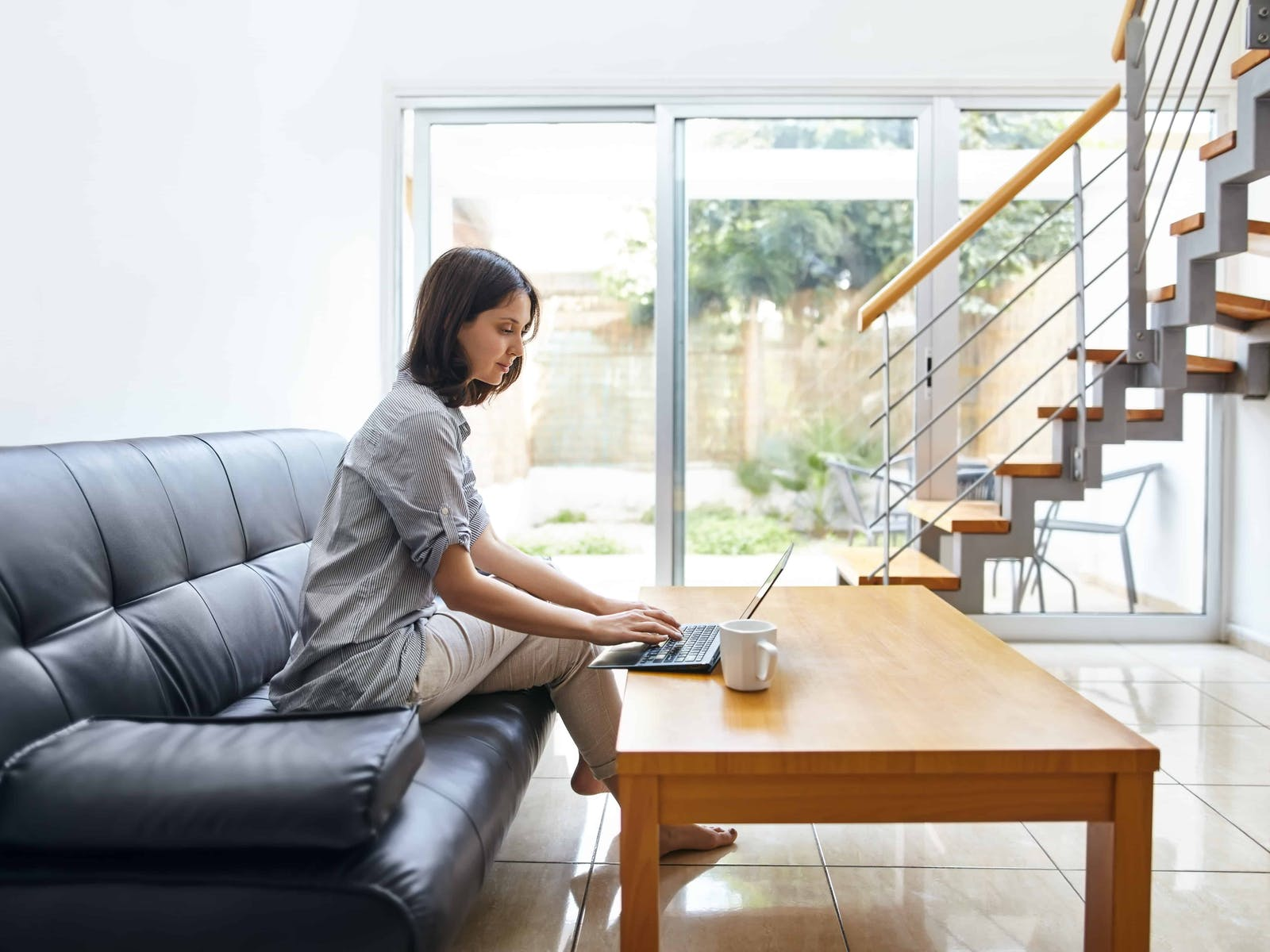Woman working on the couch in her multifamily unit