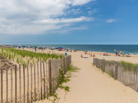 Sandy beach filled with people enjoying a beach day in Ocean City, MD