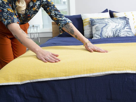 Resident smoothing out blue and yellow blanket on a bed
