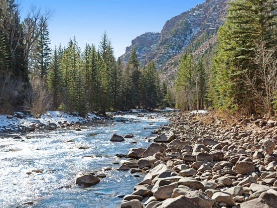 rushing river in Colorado surrounded by trees and mountains