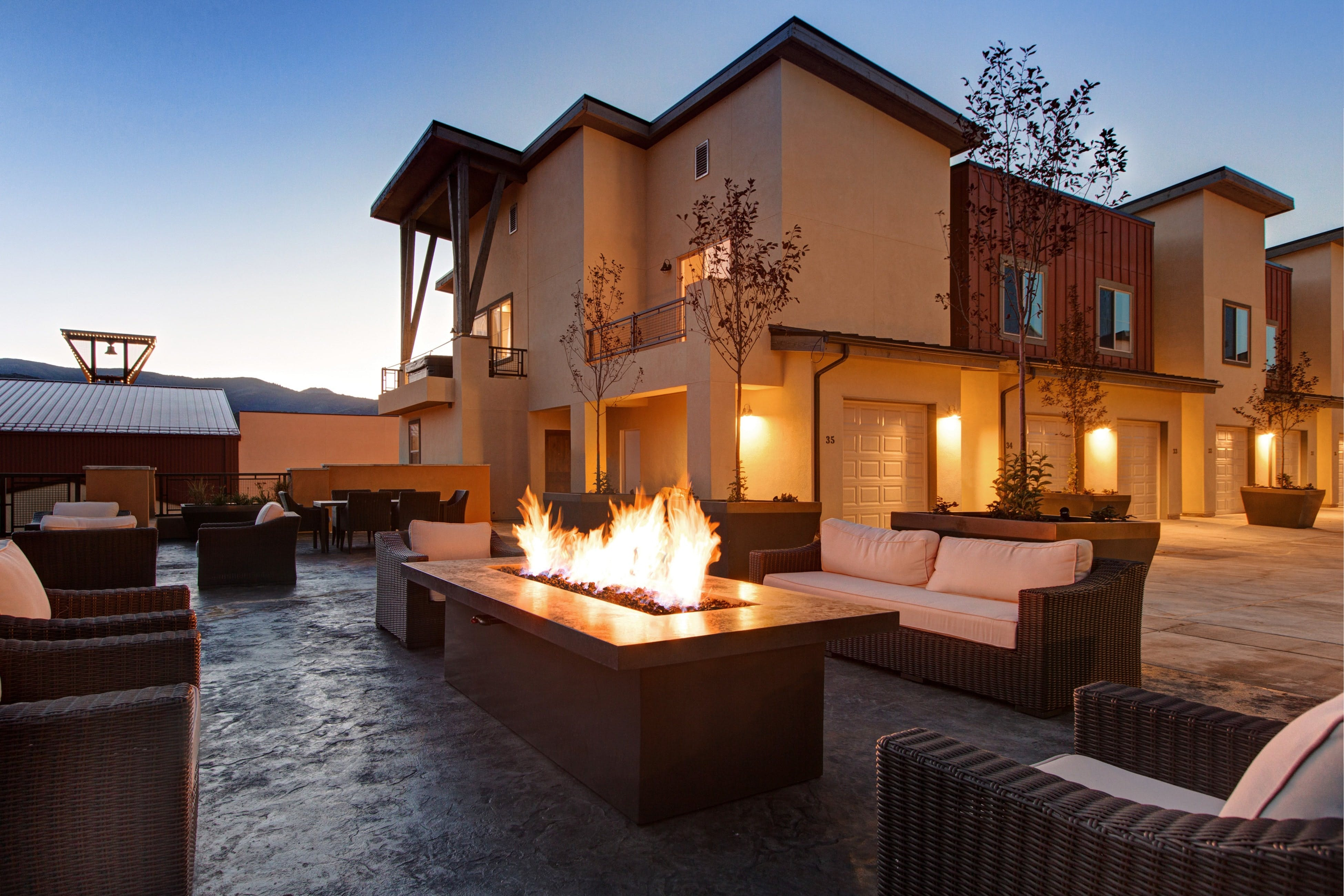 an ourdoor firepit surrounded by couches near a condo in tahoe