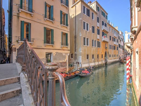 Waterway in Venice with gondolas docked near a building