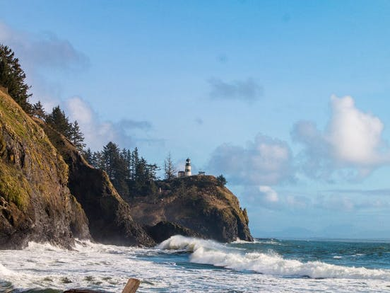 Lighthouse perched above the ocean as waves crash against the Washington coast